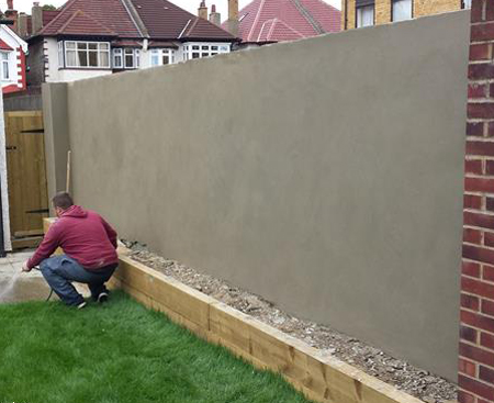 A man next to a freshly rendered garden wall in Croydon